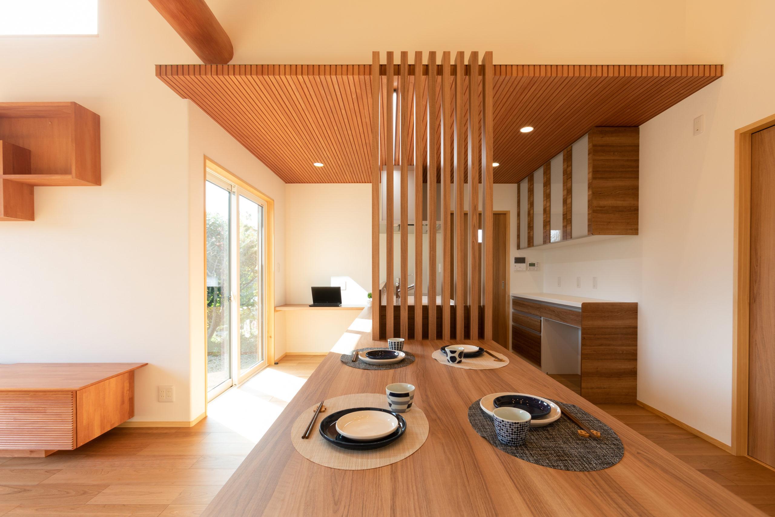 キッチンと横並びの造作ダイニングテーブルは、来客時には移動させて広々と使うことができます。横並びキッチンでも、格子でさりげなく空間に境界を。